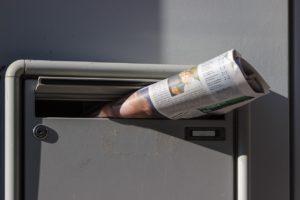 新聞紙がポストにはまっている