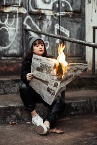 新聞が燃えている状態で新聞を読んでいる少女
