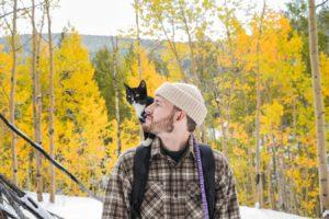 雪山を歩いてる猫と男
