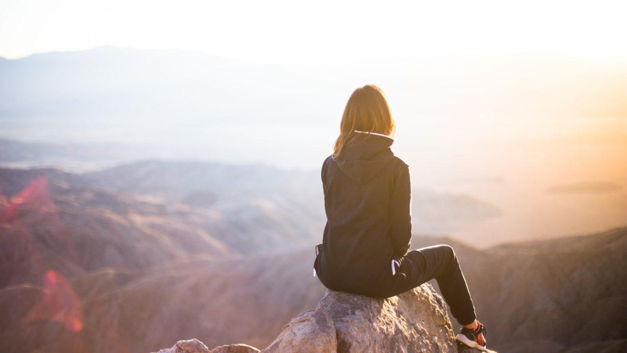 高台から遠くを見ている女性