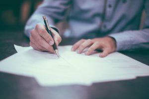字を書いている男性