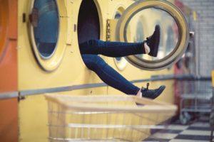 洗濯機に頭を突っ込んでる女性