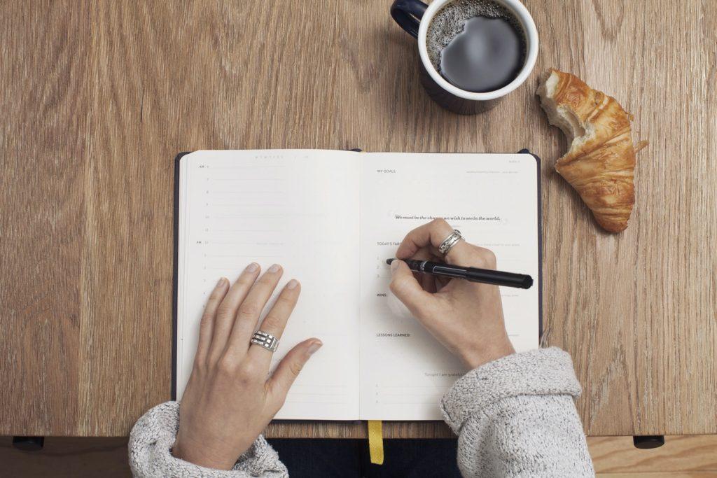 ノートに予定を書いている