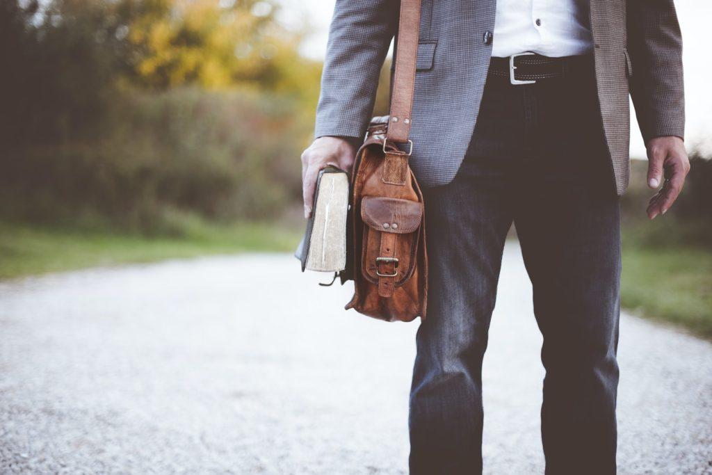 スーツを着て本を持っている男性