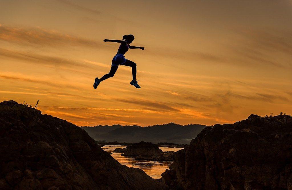 夕暮れでジャンプする人
