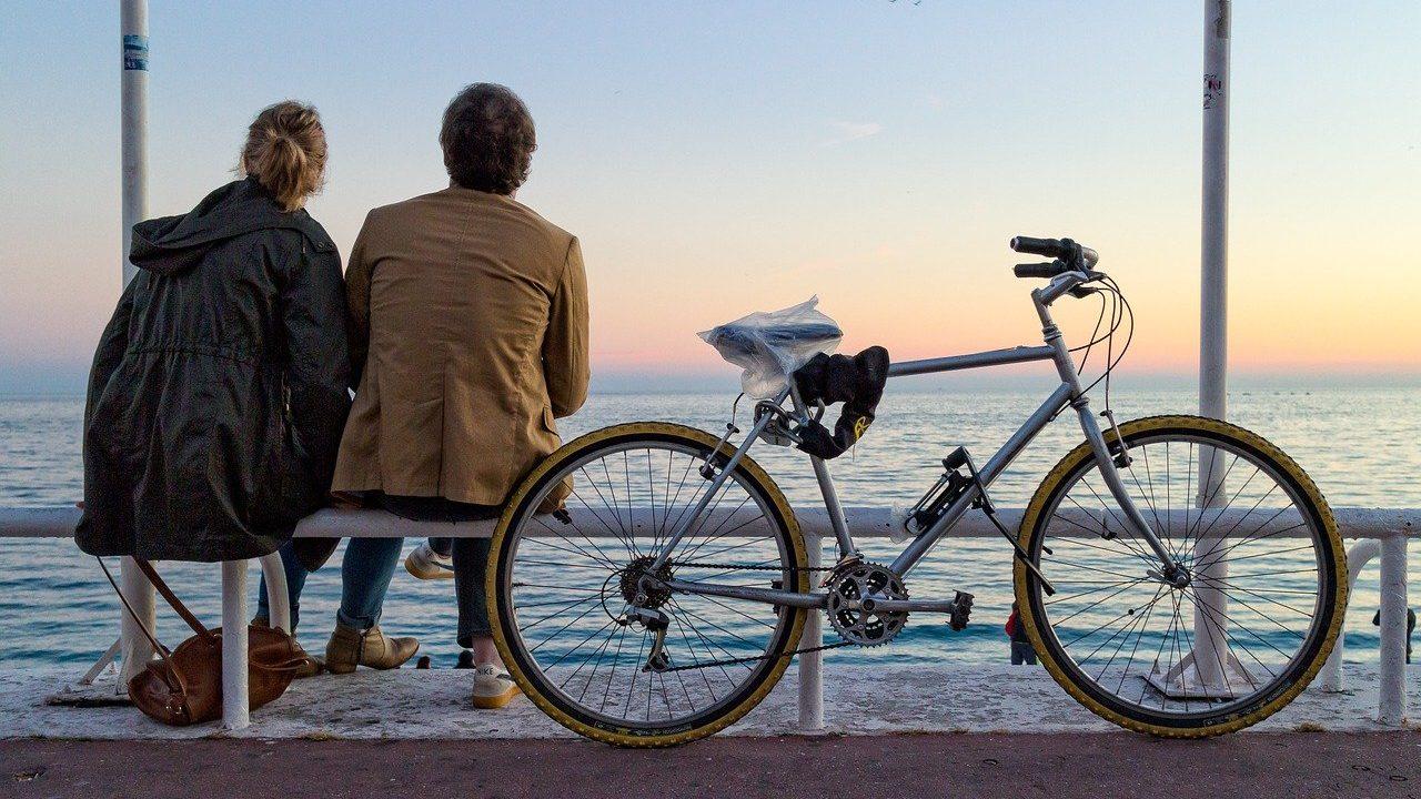 自転車の横でベンチに座っているカップル