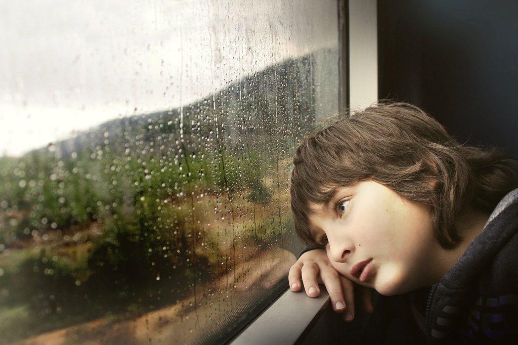窓を悲しそうに見つめる少年